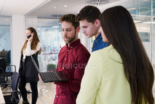 Low angle of group of cheerful young coworkers in casual clothes with laptop standing together in modern workplace and sharing news while having break during work — Stock Photo