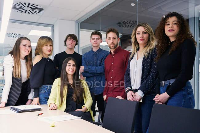 Gruppe junger kreativer multiethnischer Mitarbeiter in lässiger Kleidung trifft sich am Tisch in modernen Büroräumen und blickt in die Kamera — Stockfoto