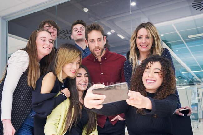 Низкий угол у группы дружелюбных коллег, улыбающихся и делающих селфи на смартфоне, собираясь на современном рабочем месте — стоковое фото