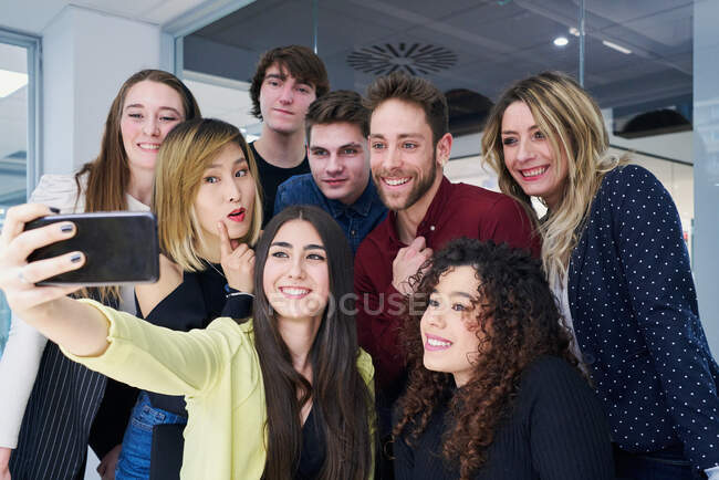 Low angle of group of friendly colleagues smiling and taking selfie on smartphone while gathering in contemporary workplace — Stock Photo