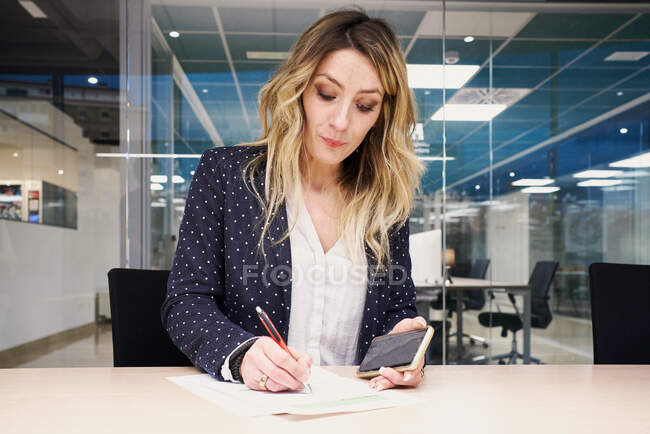 Serious young female entrepreneur in stylish outfit sitting at table with smartphone in hand and writing notes in document while working in contemporary coworking space — Stock Photo