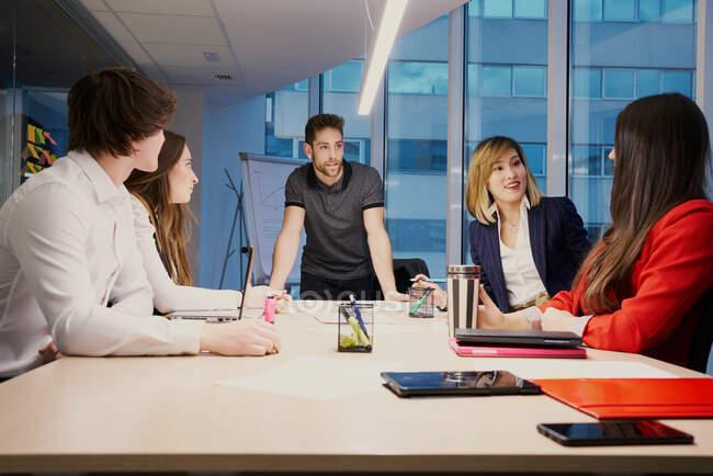 Gruppo di colleghi multirazziali che si riuniscono attorno al tavolo e discutono di progetto aziendale mentre lavorano in un ufficio moderno — Foto stock