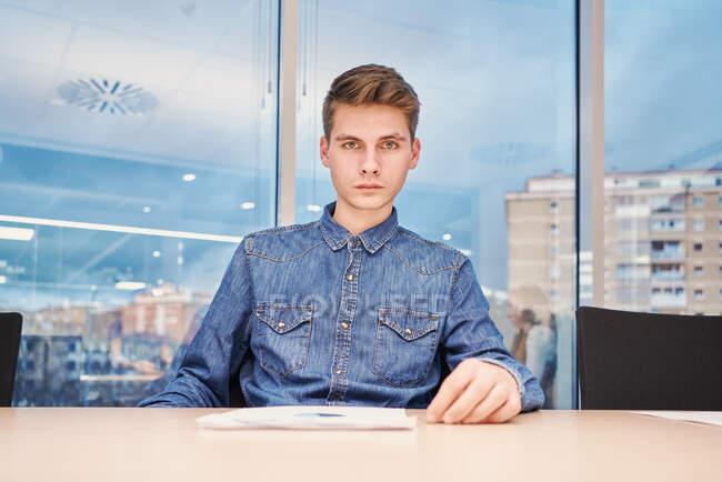 Серйозний робітник у звичайній сорочці, який сидить за столом на місці сучасної роботи і читає документи. — стокове фото