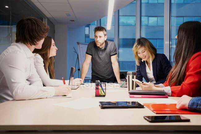 Gruppe multiethnischer Mitarbeiter, die sich um einen Tisch versammeln und Geschäftsprojekte besprechen, während sie im modernen Büro arbeiten — Stockfoto