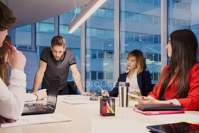 Group of multiracial coworkers gathering around table and discussing business project while working in modern office — Stock Photo