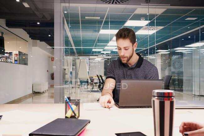 Hombre de negocios enfocado en ropa casual sentado en la mesa con el ordenador portátil y el análisis de informes mientras hace papeleo - foto de stock