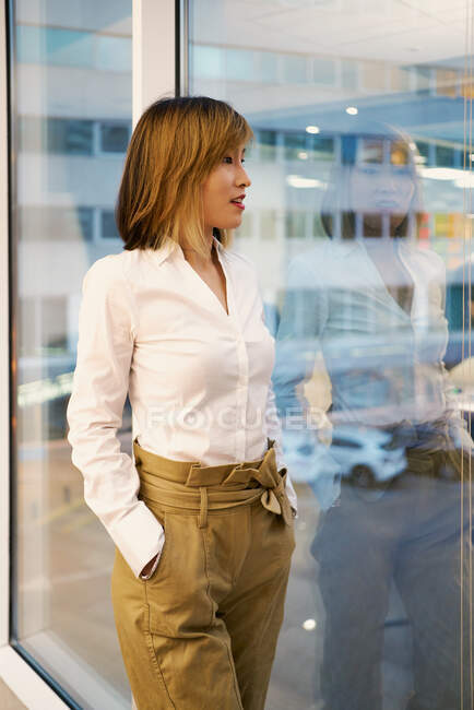 Determined female entrepreneur in classy clothes standing near window in modern coworking space and looking at camera — Stock Photo