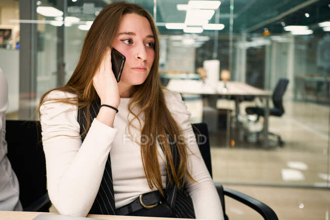 Concentrated female employee in elegant clothes sitting in office chair and using smartphone while working in modern workspace and looking away — Stock Photo