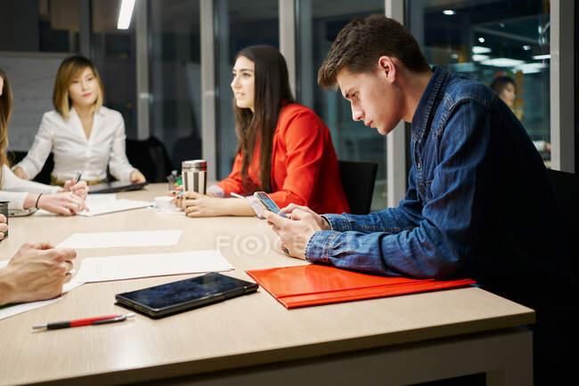 Umsichtiger männlicher Angestellter in Freizeitkleidung sitzt während eines Geschäftstreffens mit diversen Kollegen am Tisch und surft auf dem Handy — Stockfoto