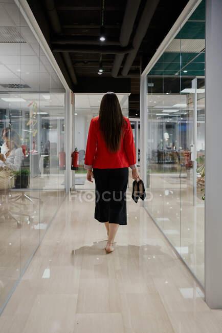 На задньому плані добре одягнена виконавча жінка з високими підборами в руці йде коридором сучасної роботи. — стокове фото