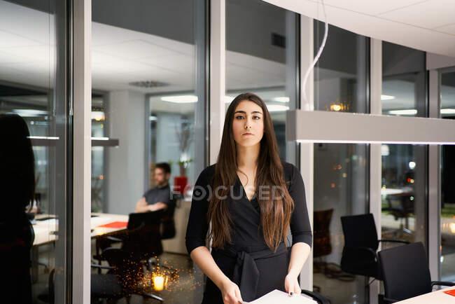 Decidida empresaria en vestido elegante de pie cerca de la mesa en la oficina contemporánea y haciendo papeleo mientras mira a la cámara - foto de stock