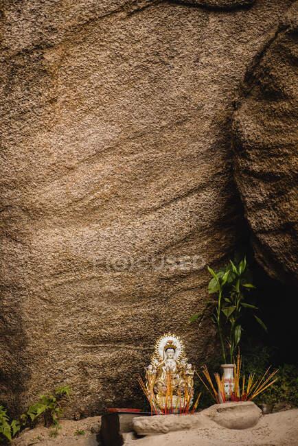 Piccola statuetta ornamentale di Buddha posta sul fondo di roccia grezza con gambo verde — Foto stock