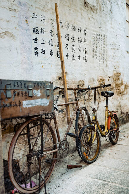 Pair of shabby bikes leaned on stone wall with drawn hieroglyphs on it — Stock Photo