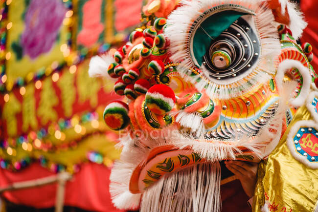 Anonymous person wearing ornamental colorful costume of dragon while performing traditional Dragon dance — Stock Photo