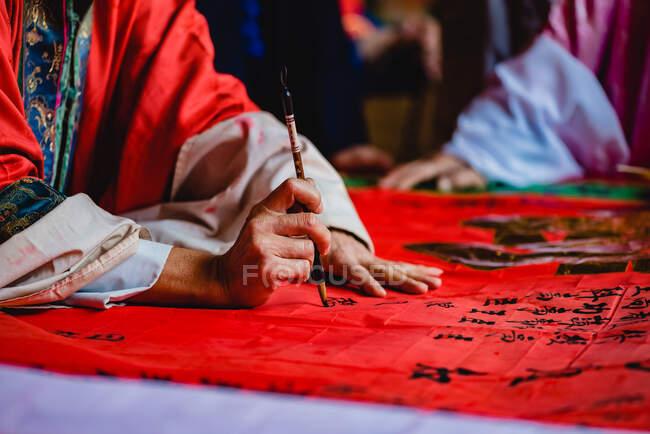 Художник з кімоно малює чорні ієрогліфи з чорнилом на червоному текстилі в храмі Гонконгу. — стокове фото