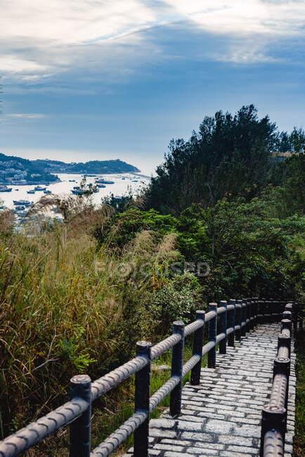 Живописный вид на зеленый берег с бухтой и маленькой дорожкой с забором и туманными горами под голубым небом с облаками — стоковое фото