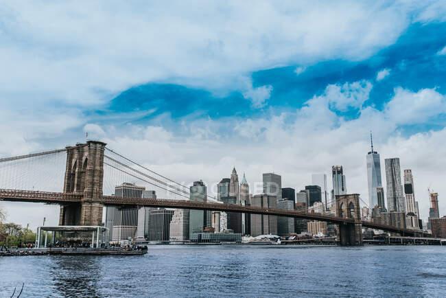 Baixo ângulo de paisagem urbana espetacular de Manhattan com suspensão Brooklyn ponte e arranha-céus no fundo do céu incrível — Fotografia de Stock