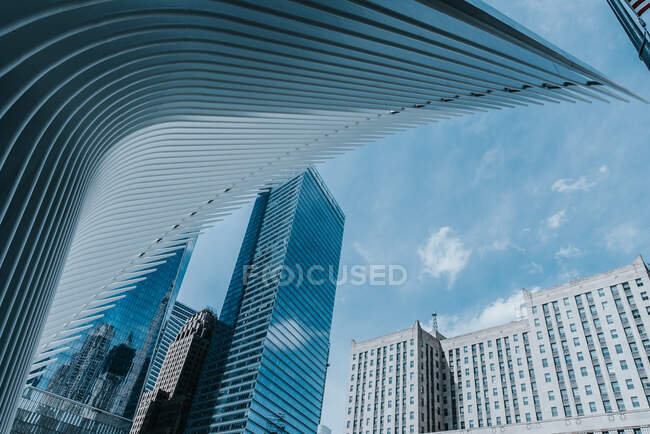 From below of contemporary skyscrapers with glass mirrored walls and futuristic construction on background of blue sky — Stock Photo