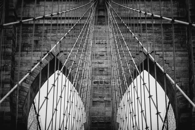 Basse inclinaison des tours en pierre avec des arches de suspension pointues Pont de Brooklyn par temps nuageux — Photo de stock