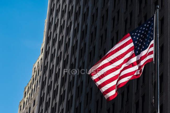 Von unten die lebendige Nationalflagge der USA, die reihenweise von einem Steingebäude über der Straße hängt — Stockfoto