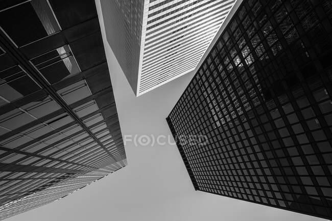 D'en bas des gratte-ciel contemporains avec des murs en verre miroir sur fond de ciel bleu — Photo de stock