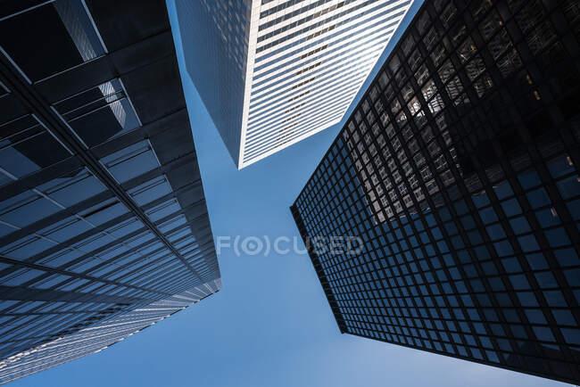 Von unten moderne Wolkenkratzer mit gläsernen Spiegelwänden vor blauem Himmel — Stockfoto