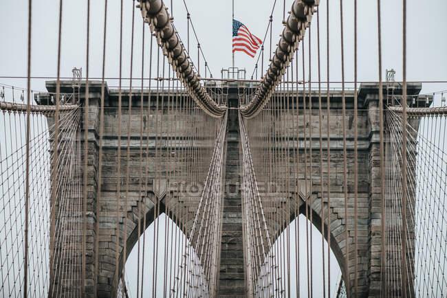 Niedriger Winkel der Steintürme mit spitzen Bögen der Hängebrücke von Brooklyn mit amerikanischer Flagge an bewölkten Tagen — Stockfoto