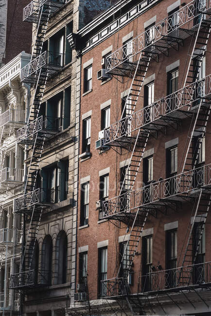 Baixo ângulo de fachadas contemporâneas com escadas de metal em Manhattan, Nova Iorque EUA — Fotografia de Stock