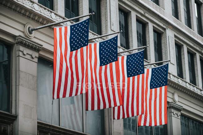 Von unten leuchten die Nationalflaggen der USA in Reih und Glied von einem Steingebäude über der Straße — Stockfoto