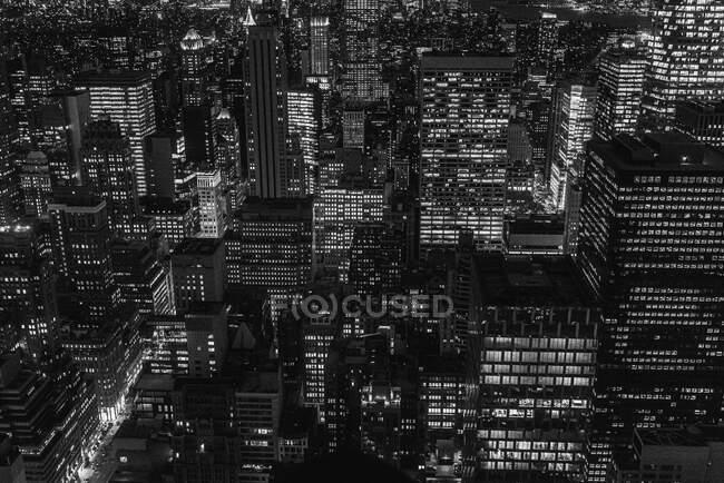 Luftaufnahme der Megalopolis mit beleuchteten Glaswänden und futuristischen Fassaden hoher Skylines im Hintergrund am Abend — Stockfoto