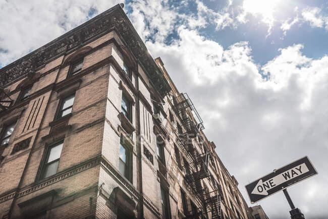 Niedriger Winkel zeitgenössischer Skylines mit Betonfassaden und Verkehrszeichen in eine Richtung auf der Straße von Manhattan — Stockfoto