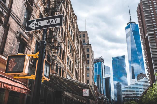 Niedriger Winkel zeitgenössischer Skylines mit Glasfassaden und Verkehrszeichen in einer Richtung auf der Straße von Manhattan — Stockfoto
