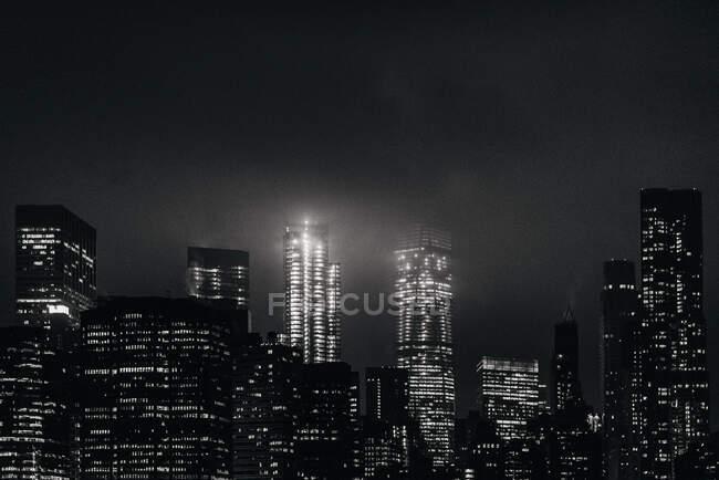 Schwarz-weißer Komplex moderner beleuchteter Skylines in Manhattan, der sich nachts vor dem ruhigen Fluss befindet — Stockfoto
