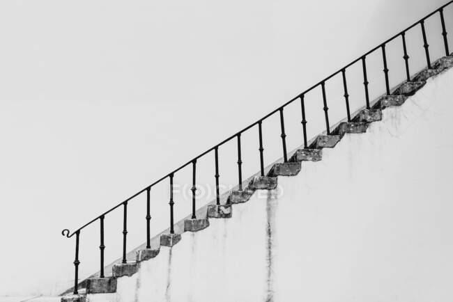 Чорно-білі обшарпані сходи з бетонними сходами і металевий баністер на задньому плані білої стіни. — стокове фото