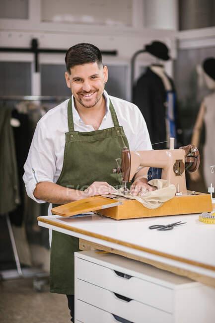 Ділігент фокусувався на чоловічому кравці в фартух, шиття одягу деталей, використовуючи сучасну швейну машину за столом, створюючи ексклюзивну колекцію одягу в сучасній студії. — стокове фото