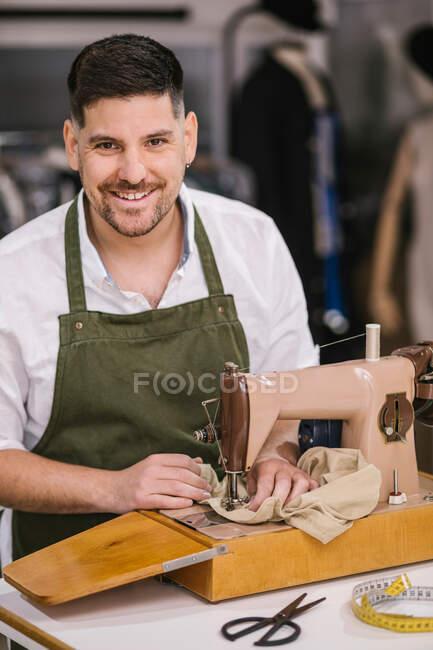 Diligente sastre masculino enfocado en detalles del traje de costura delantal utilizando la moderna máquina de coser en la mesa mientras crea una colección exclusiva de ropa en el estudio de trabajo contemporáneo - foto de stock