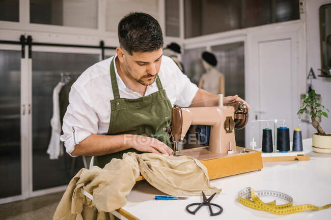 Diligent focused male tailor in apron sewing outfit details using modern sewing machine at table while creating exclusive clothes collection in contemporary work studio — Stock Photo