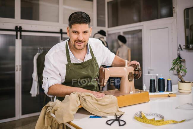 Усердный счастливый портной в фартуке швейная одежда детали с помощью современной швейной машины за столом, создавая эксклюзивную коллекцию одежды в современной рабочей студии — стоковое фото