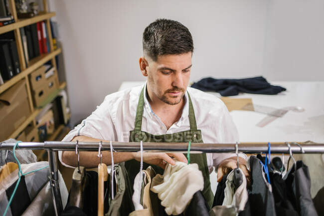 High angle of serious focused male tailor in apron checking details of apparel hanging on hanger on metal rack among other trendy bespoke clothes in modern workroom — Stock Photo
