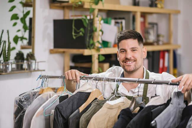 Alto angolo di felice focalizzata sarto maschile in grembiule controllare i dettagli di abbigliamento appeso sul portapacchi in metallo tra gli altri vestiti alla moda su misura in sala da lavoro moderna — Foto stock