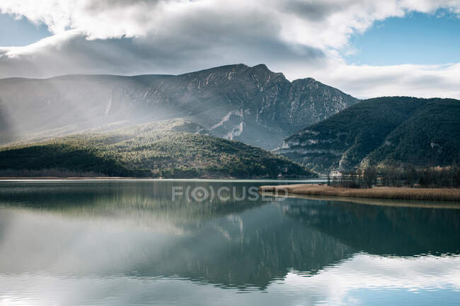 Majestic rocky mountains of Montsec Range reflected in water of calm lake in cloudy day in Spain — Stock Photo