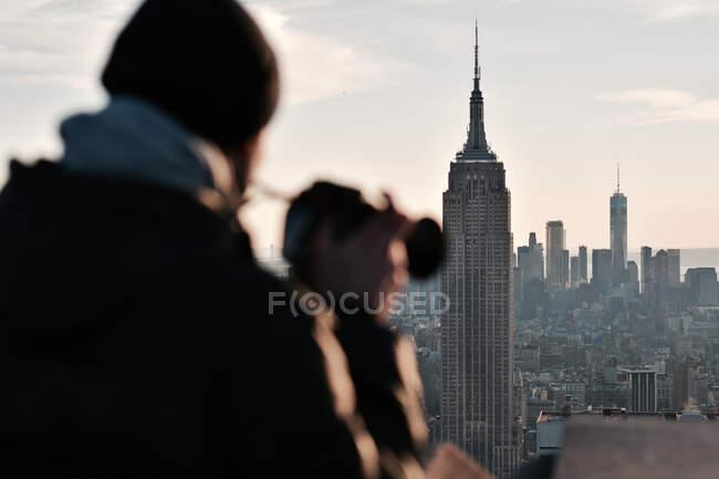 Vista posterior del viajero masculino anónimo con cámara fotográfica observando la ciudad con altos horizontes durante el atardecer - foto de stock