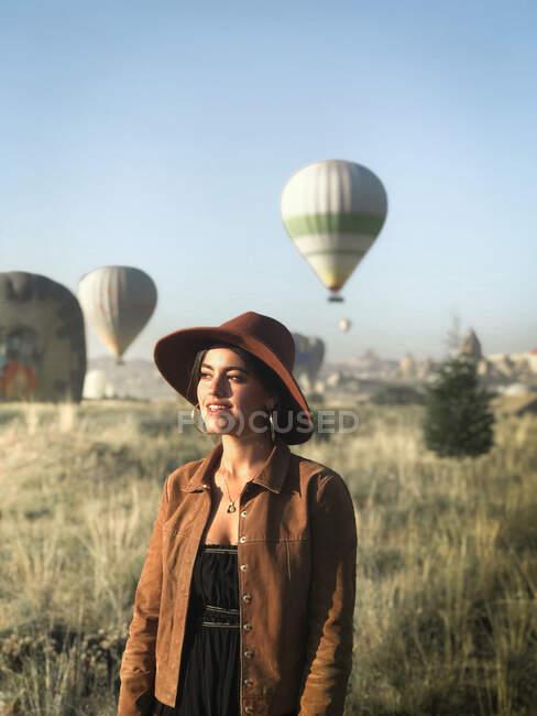 Turista sonriente en ropa de moda de pie en el campo verde y disfrutando de un clima soleado en el fondo de globos de aire caliente - foto de stock