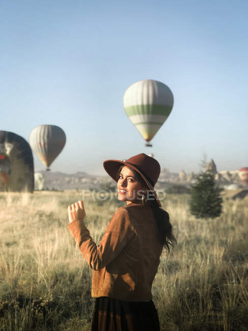 Smiling female tourist in trendy wear standing in green field and enjoying sunny weather on background of hot air balloons — Stock Photo