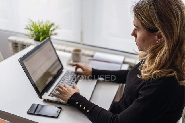 From above of focused young female in casual outfit sitting at table with laptop and working online in light workplace at home — Stock Photo