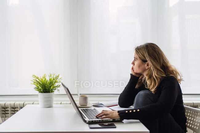 High angle side view of focused female specialist in casual wear working with electronic documents on laptop while sitting at table near window in modern room at home — Stock Photo