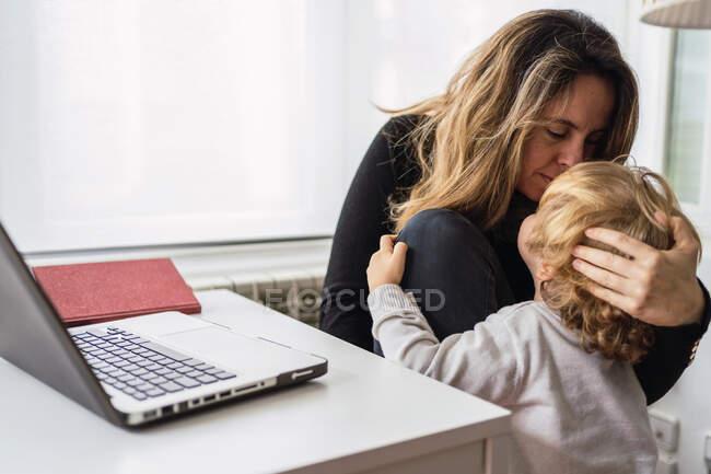 Moderna empresaria ocupada en ropa casual abrazando y besando a un niño pequeño mientras trabaja en el proyecto con el ordenador portátil en la oficina en el hogar - foto de stock