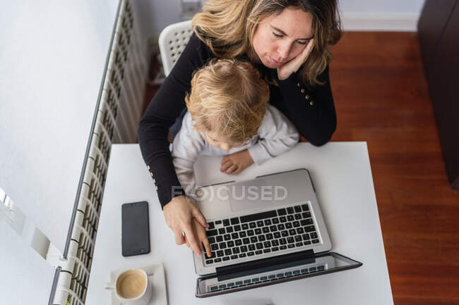 Von oben hält eine Mitarbeiterin ein neugieriges kleines Kind auf Knien, während sie am Tisch sitzt und zu Hause mit dem Laptop arbeitet — Stockfoto