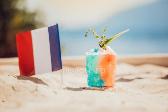 Склянка відсвіжного алкогольного напою і французький прапор на піску. — стокове фото