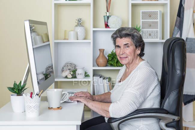 Літня жінка у повсякденному одязі сидить у кріслі за столом і піднімає руки, щоб відсвяткувати чудові новини, спостерігаючи за комп
